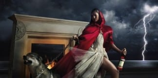 sexxy woman with wolf on chain outside in front of fireplace with lightening in the background